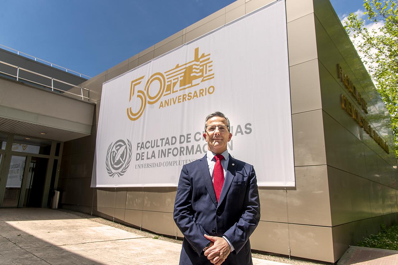 Jorge Clemente posa hace escasos días ante el cartel que conmemora el 50º aniversario de la Facultad, instalado en la entrada del aulario del centro / Fotografía: Jesús de Miguel