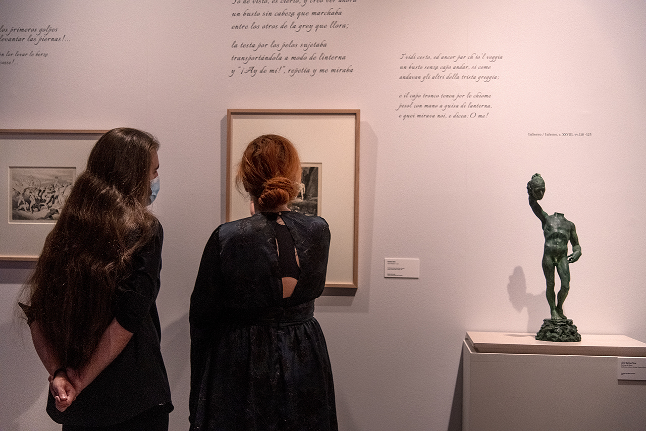 """Visitantes en la exposición """"La Divina Comedia. Inspiración y razón"""". A la derecha, la escultura de Javier Martínez Pérez"""