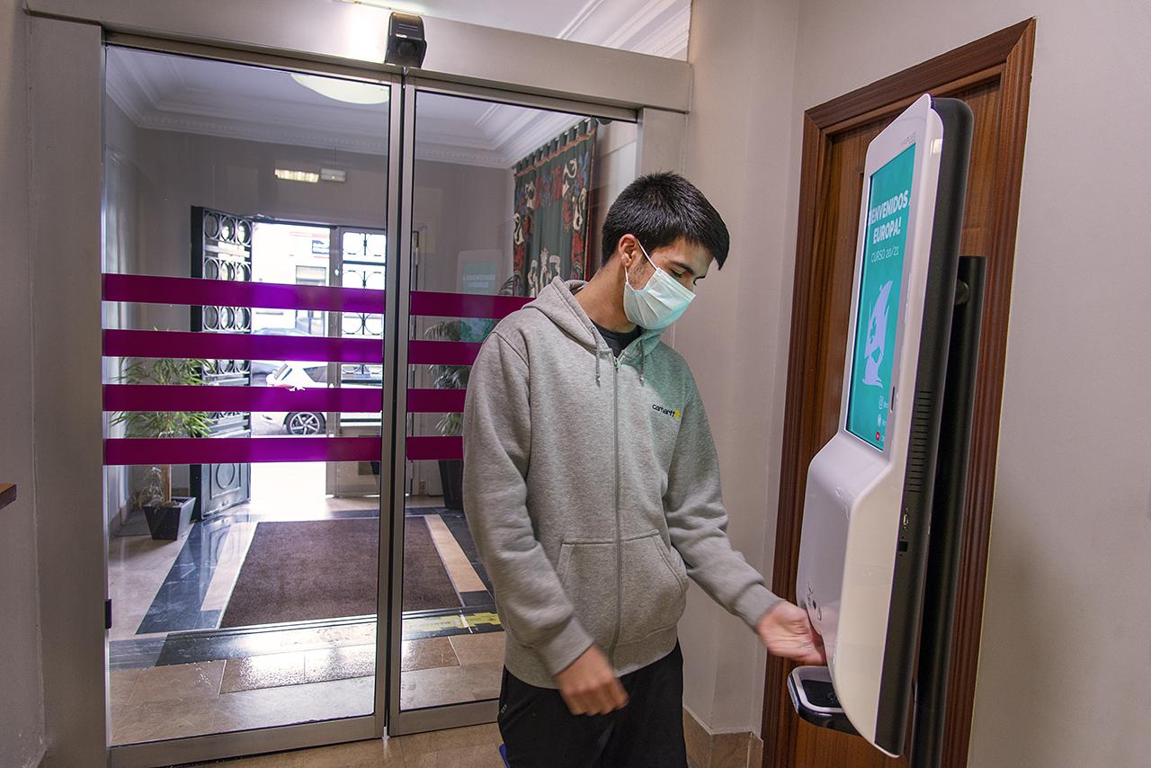 Un colegial utiliza un dispensador automático de gel hidroalcohólico