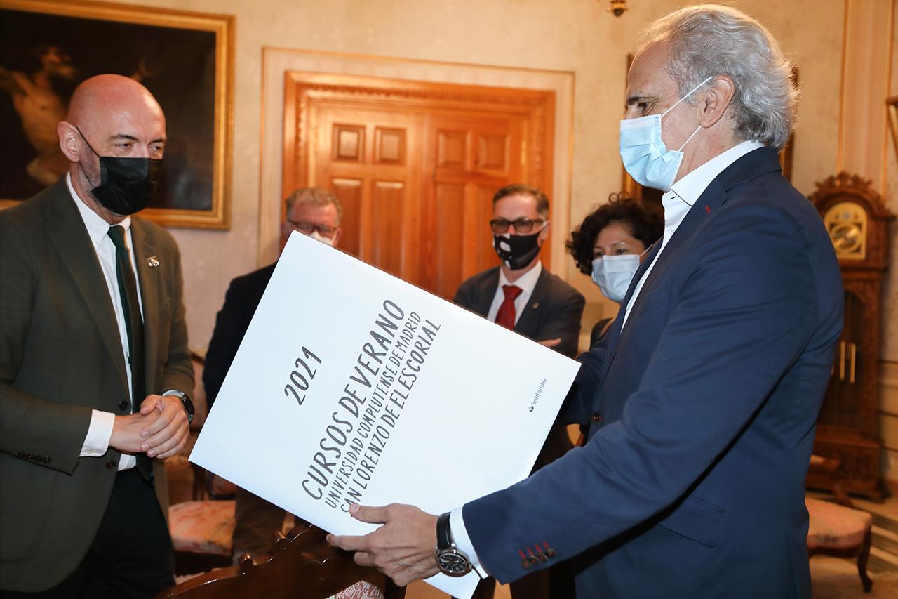 El rector entrega al consejero una copia del cartel de esta edición de los Cursos de Verano, realizado por Óscar Mariné